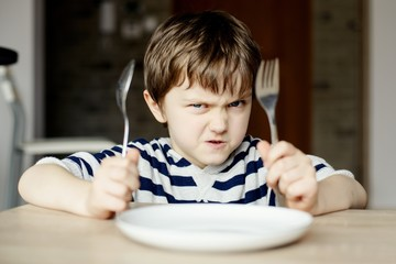 Furious little boy waiting for dinner