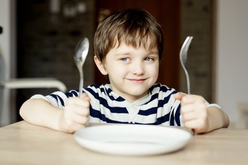 Happy little boy waiting for dinner.