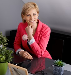 Happy businesswoman sitting at desk