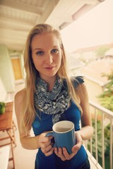 Portrait of young blonde woman in balcony