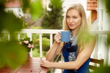 Portrait of young blonde woman drinking tea