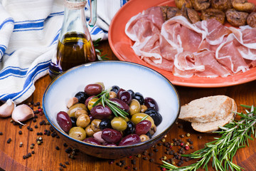 Olives in bow with prosciutto on wooden table