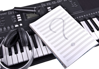 headphones, a microphone and a notebook for musical notes