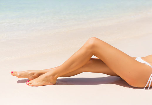 Beautiful slim woman's legs on the beach
