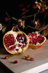 Pomegranate fruit on wooden board and depth of flowers