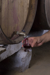 Someone pours wine from a barrel