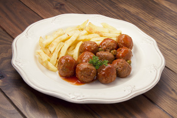 Deatballs with peas, sauce and french fries, over a wooden table