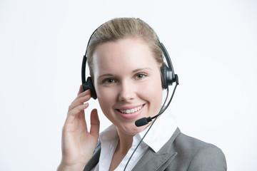 Hübsche Frau mit Headset lächelt in die Kamera