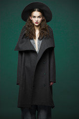 fashion model woman coat and hat urban style pose on color