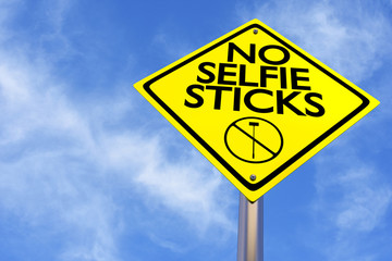A no selfie sticks sign on a blue sky background.