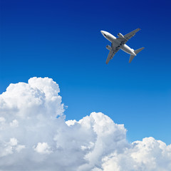 Canvas Print - Airplane flying in the blue sky with clouds