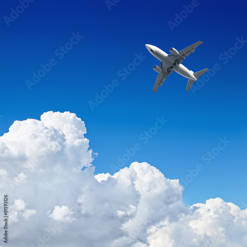 Wall mural Airplane flying in the blue sky with clouds
