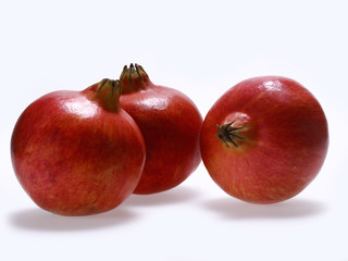 Several whole pomegranate on a white background