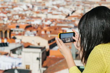 Young Woman Taking Mobile Pictures from a City Viewpoint