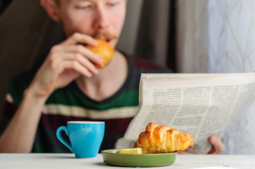 Breakfast with coffee and croissant with young man on backgroung