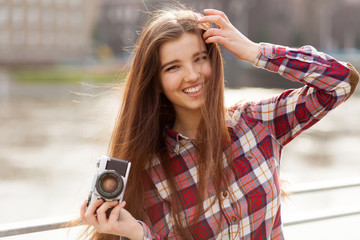 Portrait of a young woman with photo camera