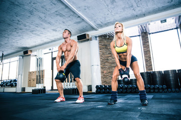 Muscular man and fit woman lifting kettle ball