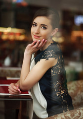 Beautiful young brunette woman sitting dreamy near a window