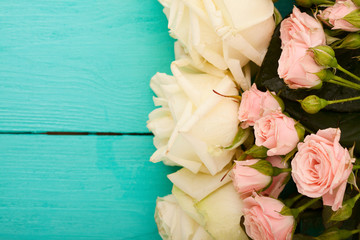 Macro roses on blue wooden background. Top view