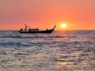 Traditional thai longtail boat against sunset above ocean, Thail