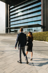 Business Couple Walking in the Street Besides a Financial Area