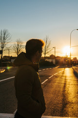 Young Man Standing in the Middle of the Road Looking at Sunset