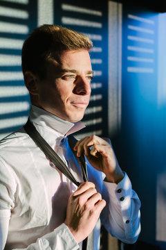 Man Adjusting The Tie