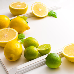 Fresh green and yellow citrus fruits on the white table.