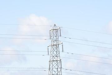 Electricity pylon with a light blue cloudy sky background.