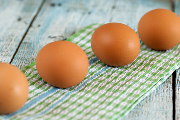Eggs and dish towel on old wooden table