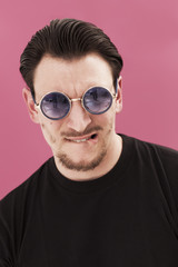 Handsome man portrait biting his lip and wearing sunglasses
