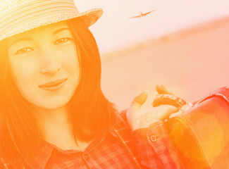 Smiling tourist girl with suitcase. Image with sunlight effect