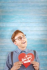 Wall Mural - Composite image of geeky hipster holding a heart card