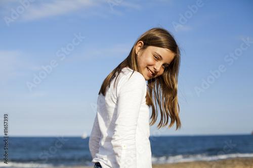 780e824ef Niña de pelo castaño con camisa blanca en la playa