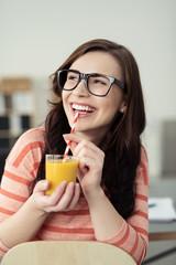 lachende frau trinkt einen smoothie am schreibtisch