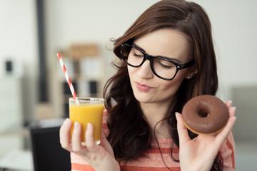 junge frau hält smoothie und donut in den händen
