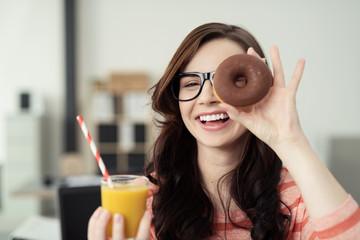lachende frau hält donut vor die augen
