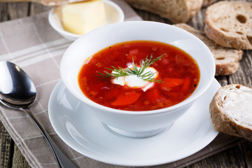 Tasty soup with bread on a wooden background.