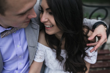 Young European couple cuddling on a park bench