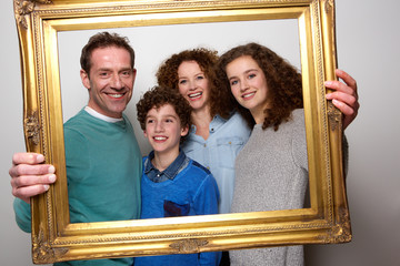 Happy family holding picture frame and smiling