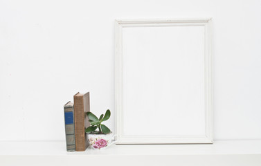 Empty picture frame and vintage books