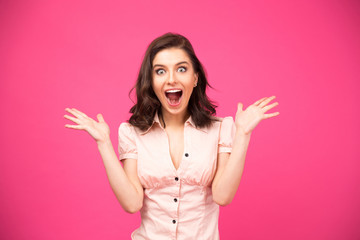 Surprised woman shouting over pink background