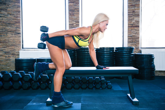 Woman workout with dumbbell on the bench