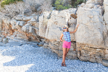 Girl standing at the rock on the shore of the Mediterranean Sea