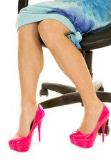 woman legs in pink heels and blue dress sitting feet pointed to