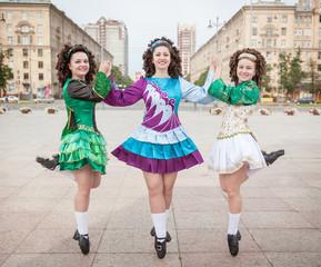 Three women in irish dance dresses and wig posing