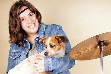 Studio shot of a young lady holding a little dog
