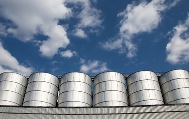Cereal silos under the cloudy blue sky