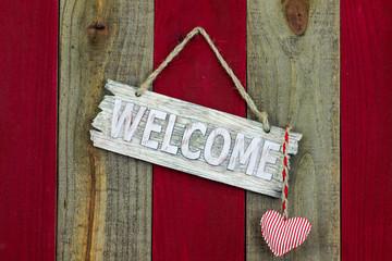Welcome sign with heart hanging on rustic wood door
