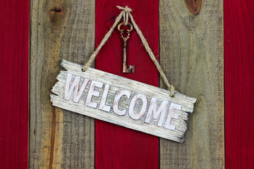 Welcome sign with skeleton key hanging on red wood door